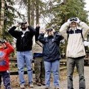 A group of people look through binoculars